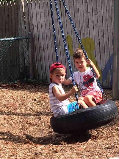Two boys swing on tire