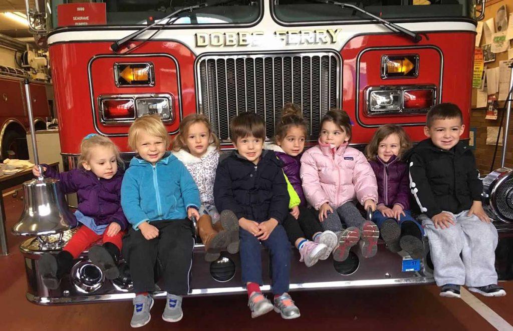 Kids sitting on firetruck fender