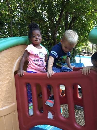 Boy and girl play on jungle gym