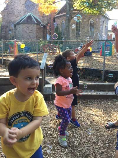 Kids blowing bubbles outside