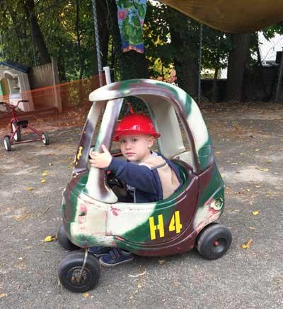Boy outside sitting in toy car