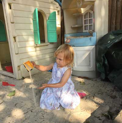 Girl digs with shovel in sandbox